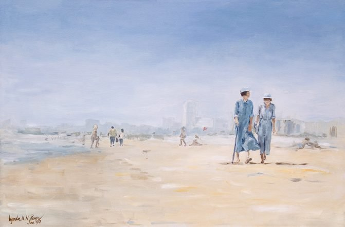 two women walking on the beach wearing denim dresses